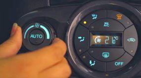 Motorista acionando ar condicionado do carro para maior conforto